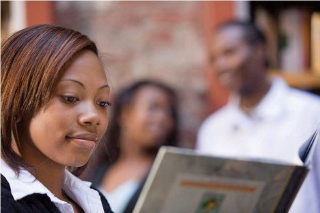 African American female student reading a book.