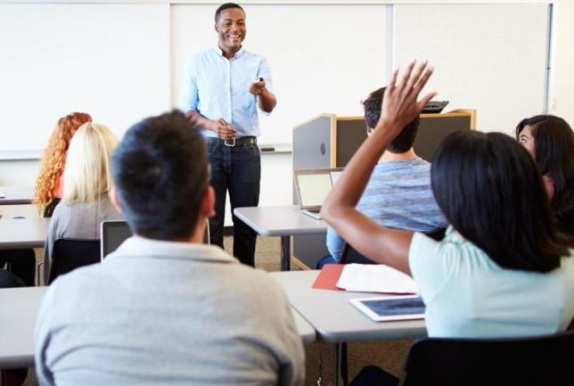 male-teacher-with-classroom-of-college-students