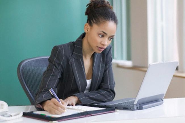 Businesswoman taking notes at her desk --- Image by © Jose Luis Pelaez, Inc./Blend Images/Corbis