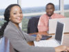 Business man and woman working on laptops in office